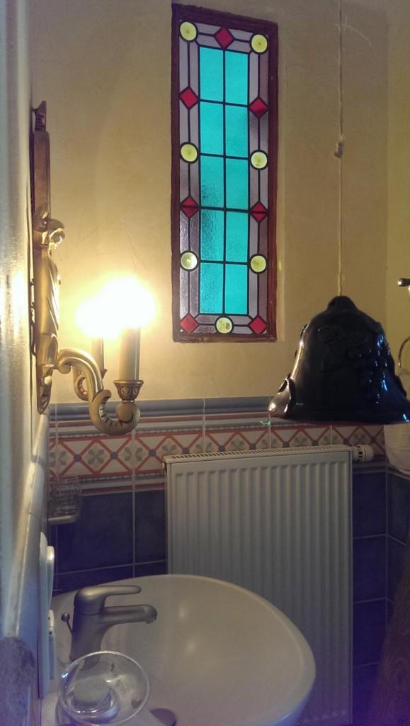 Das Badezimmer mit Bleiglasfenster.